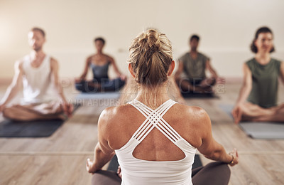 Buy stock photo Rearview shot of a yoga instructor instructing her class in studio
