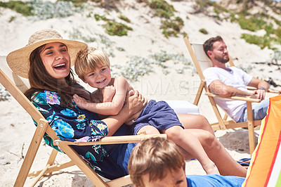 Buy stock photo Shot of a mother and her little son sitting on a deck chair at the beach with their family