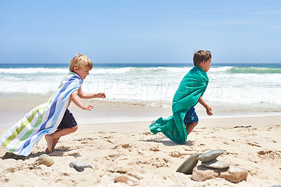 Buy stock photo Shot of two adorable little boys running with towels wrapped around them at the beach