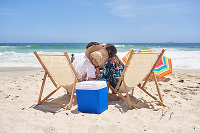 Buy stock photo Shot of a mother and father giving each other a kiss while covering their faces with a sunhat at the beach