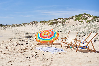 Buy stock photo Shot of an umbrella, blanket and deck chairs set up on a beach