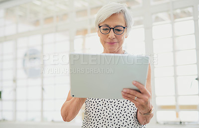 Buy stock photo Shot of a senior businesswoman using a digital tablet in a modern office