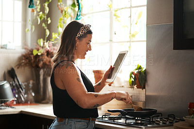 Buy stock photo Shot of a young woman using a digital tablet while preparing a meal at home