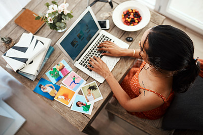 Buy stock photo High angle shot of an unrecognizable businesswoman sitting in her home office and blogging from her laptop