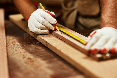 Buy stock photo Closeup of an unrecognizable male carpenter doing measurements on a piece of wood inside of a workshop at night