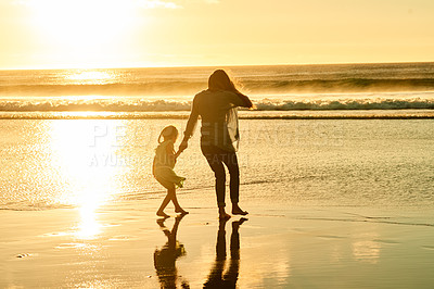 Buy stock photo Rearview shot of a woman walking on the beach with her young daughter
