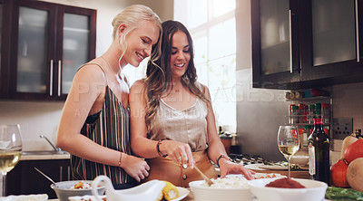 Buy stock photo Shot of a happy young couple having wine while preparing a meal at home