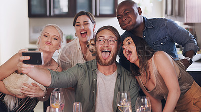 Buy stock photo Shot of a group of young friends taking selfies during a get together at home