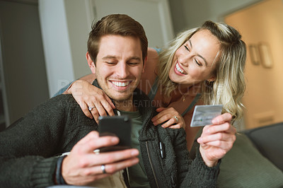 Buy stock photo Shot of a young couple using a credit card and smartphone on the sofa at home