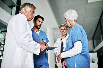 Buy stock photo Cropped shot of a diverse group of medical practitioners having a discussion while standing in a hospital
