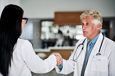 Buy stock photo Cropped shot of a handsome mature male doctor shaking hands with a young female doctor in a hospital