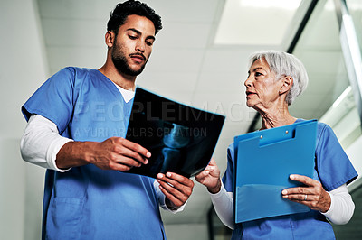 Buy stock photo Cropped shot of two medical practitioners discussing a  radiological image while standing in a hospital