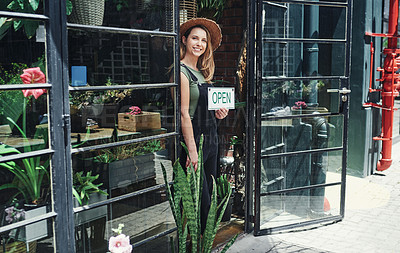 Buy stock photo Cropped portrait of an attractive young business owner standing alone and holding the open sign at the floristry entrance