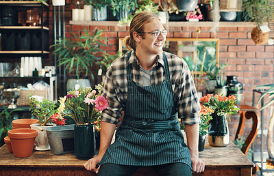 Buy stock photo Cropped shot of a handsome young businessman sitting alone in his flower shop during the day