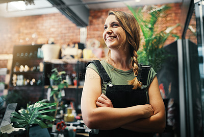 Buy stock photo Cropped shot of an attractive young business owner standing in her floristry alone with her arms folded