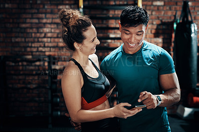Buy stock photo Cropped shot of two young sportspeople using a smartphone together in a gym
