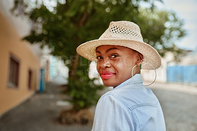 Buy stock photo Portrait of an attractive young woman looking back at the camera while wearing a hat outside during the day