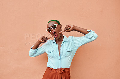 Buy stock photo Cropped shot of a cheerful young woman posing while standing against a orange background outside during the day