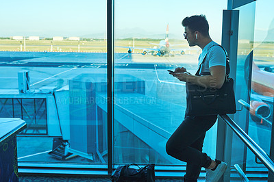 Buy stock photo Shot of a young man using a smartphone in an airport