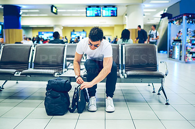 Buy stock photo Shot of a young man closing his bags on preparation for a flight at the airport