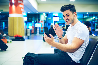 Buy stock photo Shot of a young man using a smartphone to make a video call at an airport