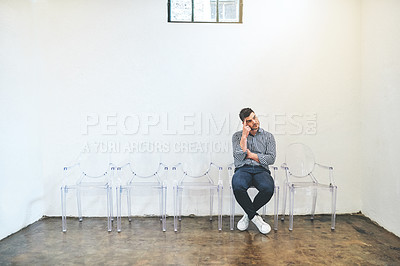 Buy stock photo Shot of a young man looking thoughtful while sitting on a chair against a white wall