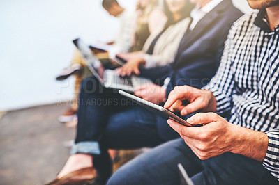 Buy stock photo Closeup shot of an unrecognisable group of candidates using digital devices while waiting in line