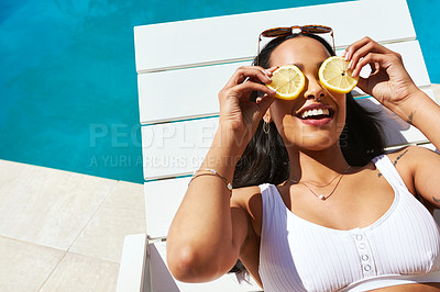 Buy stock photo Cropped shot of a young woman posing with lemon slices over her eyes by the poolside