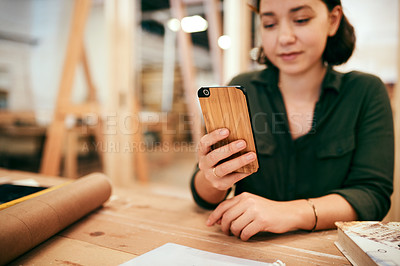 Buy stock photo Cropped shot of a female carpenter using her cellphone while sitting in her workshop