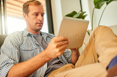 Buy stock photo Shot of a young man using a digital tablet while relaxing on the sofa at home