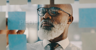 Buy stock photo Shot of a mature businessman brainstorming and writing on adhesive notes on a glass wall inside his office