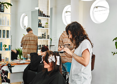 Buy stock photo Cropped shot of an attractive young hairdresser standing and applying hair dye on her client in a salon