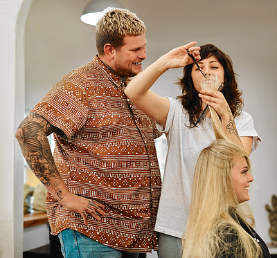 Buy stock photo Cropped shot of an attractive young hairdresser standing with a colleague while cutting a client's hair in her salon