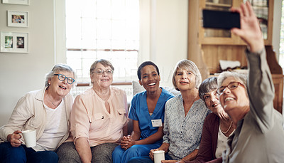 Buy stock photo Cropped portrait of a happy senior woman using her cellphone to take a selfie with her friends and nurse