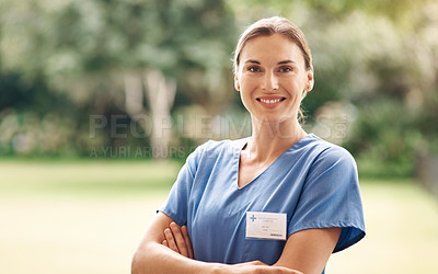 Buy stock photo Portrait of a confident young nurse standing outside in the garden of a retirement home