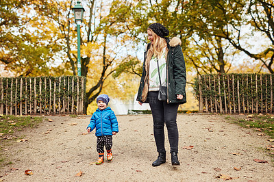 Buy stock photo Full length shot of an affectionate young mother walking through a park with her little son in autumn