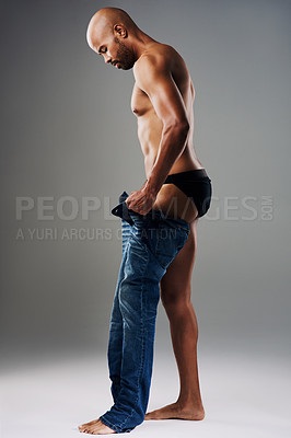 Buy stock photo Full length shot of a handsome young man undressing against a grey background