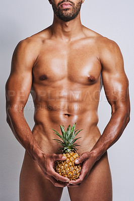 Buy stock photo Cropped shot of an unrecognizable naked man posing with a pineapple covering his genital area against a grey background