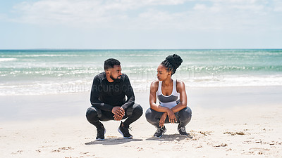 Buy stock photo Shot of a confident young couple seated on the ground together while looking into each other's eyes outside on a beach during the day