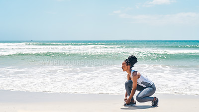 Buy stock photo Shot of a confident young woman tying her shoe laces before doing training exercises outside on a beach during the day