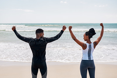 Buy stock photo Rearview shot of a cheerful young couple raising their arms in the air in success at the ocean while standing on a beach outside during the day
