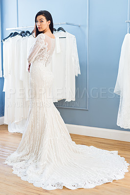 Buy stock photo Full length portrait of a beautiful young bride fitting her wedding gown in a bridal shop