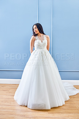 Buy stock photo Full length shot of a beautiful young bride looking away thoughtfully while wearing her wedding gown in her dressing room