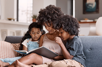 Buy stock photo Shot of a happy young mother reading a book and spending time with her two children at home
