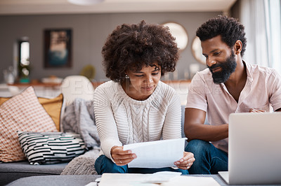 Buy stock photo Shot of a couple looking at paperwork while using a laptop in their living room