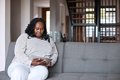 Buy stock photo Shot of an attractive mature woman using a digital tablet while relaxing on a sofa at home