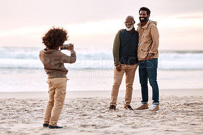 Buy stock photo Shot of an adorable little boy taking a photo of his father and grandfather with a smartphone at the beach