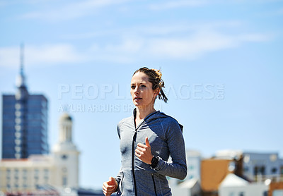 Buy stock photo Cropped shot of a beautiful young woman out for a run in the city