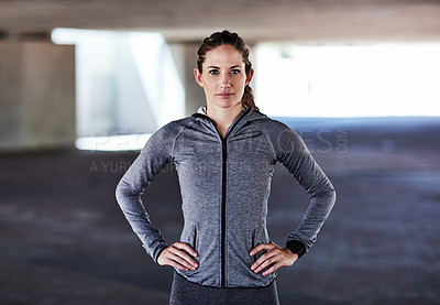 Buy stock photo Cropped portrait of an attractive young female athlete standing with her hands on her hips while working out in the city