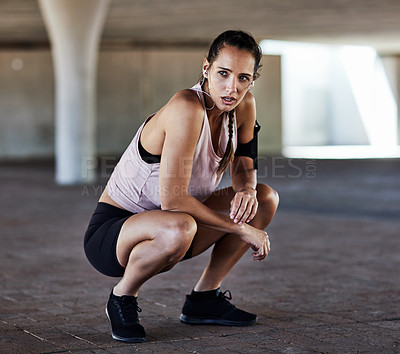 Buy stock photo Full length shot of an attractive young female athlete resting during her workout in the city
